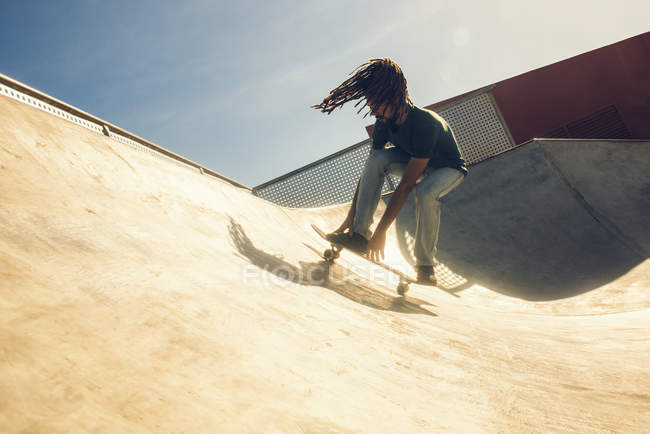 Young man with dreadlocks skateboarding in a skatepark — Stock Photo