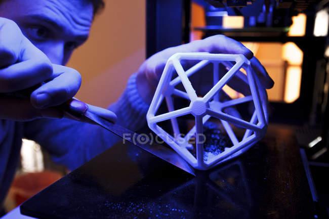 Hombre usando una espátula para separar una figura geométrica 3D de la plataforma de una impresora 3D - foto de stock