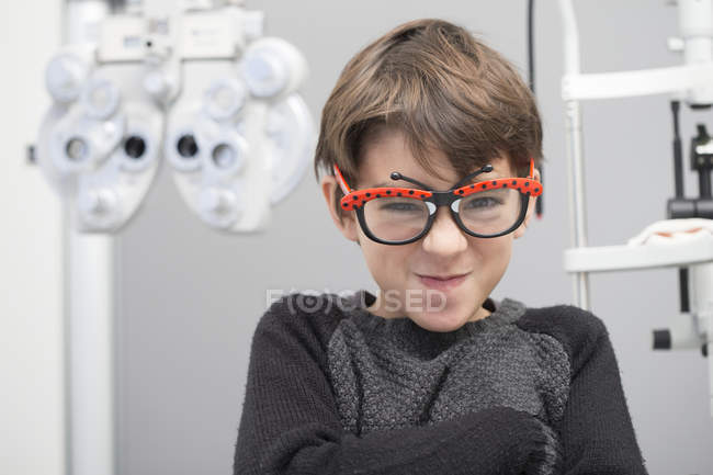 Portrait of smiling boy in eyeglasses at an optician shop — Stock Photo