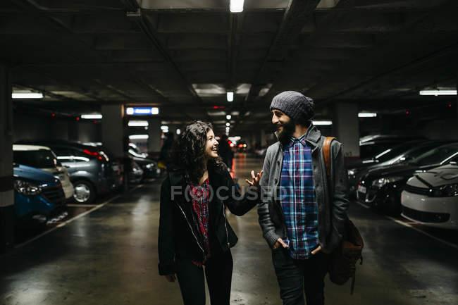Couple walking and talking in parking garage — Stock Photo