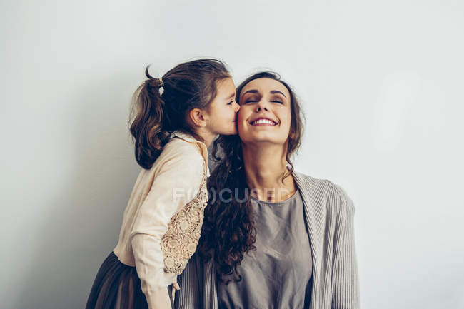 Дочка цілуватися усміхнений матері щоку — стокове фото