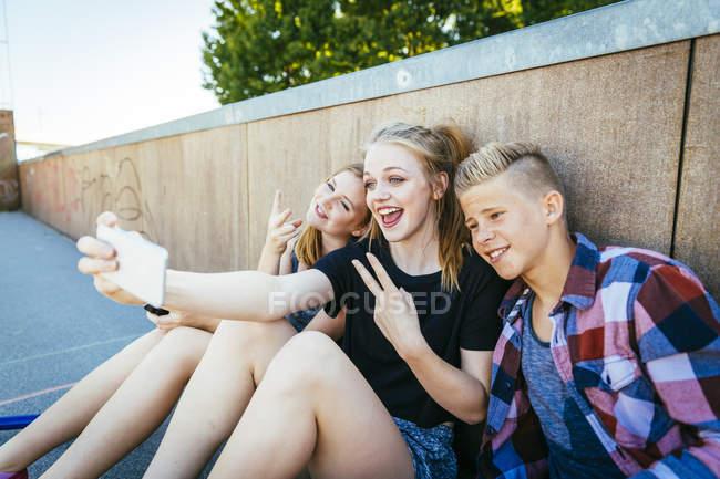Trois adolescents heureux en plein air prenant un selfie — Photo de stock
