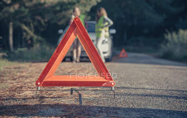 Triângulo de aviso na estrada por um carro avaria com as mulheres em segundo plano — Fotografia de Stock