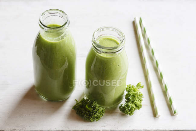 Two glass bottles of kale smoothie with drinking straws — Stock Photo