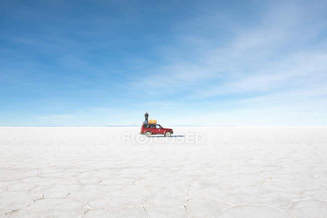 Bolivien, Salar de Uyuni, Altiplano, Atacama Mann stand am Autodach in Wüste — Stockfoto