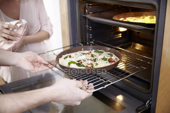 Couple mettant la pizza au four, vue de la section médiane — Photo de stock