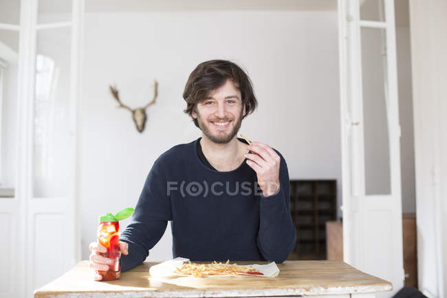 Portrait of smiling young man eating French fries with ketchup — Stock Photo