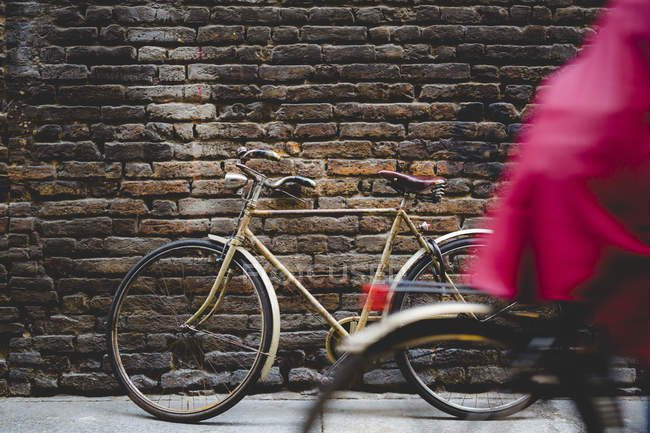 Vintage bicycle leaning against a brick wall while cyclist passing by — Stock Photo