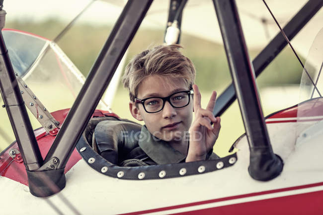 Boy sitting in biplane showing victory sign — Stock Photo