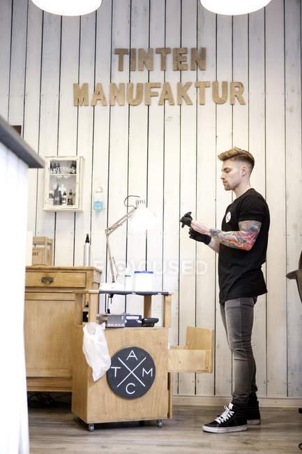 Tattooist in his tattoo studio side view — Stock Photo