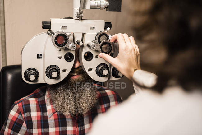 Bearded man at the optometrist making an eye test — Stock Photo