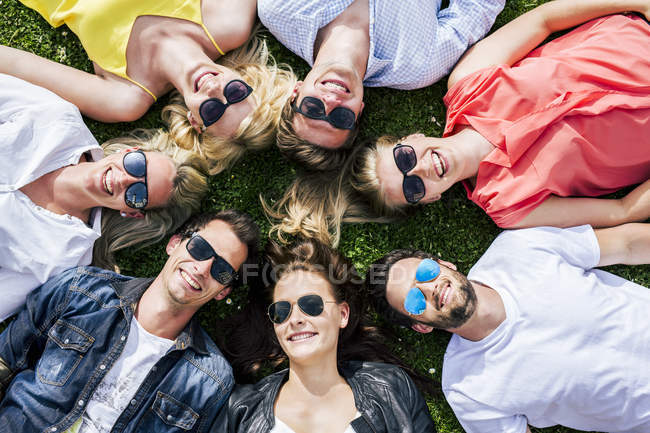 Happy friends wearing sunglasses lying in meadow together — Stock Photo