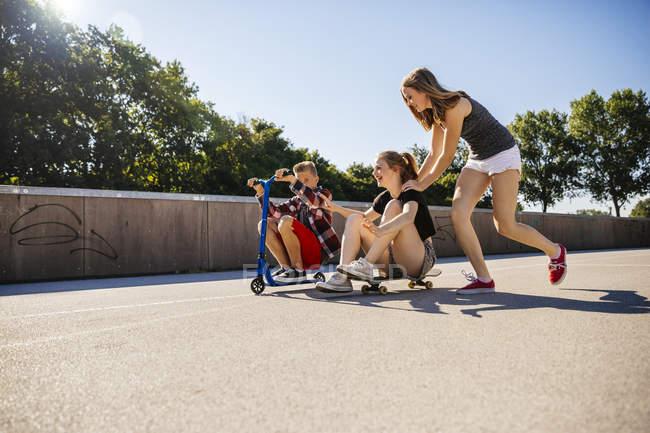 Три игривый подростковой друзей, весело с скутер и скейтборд — стоковое фото