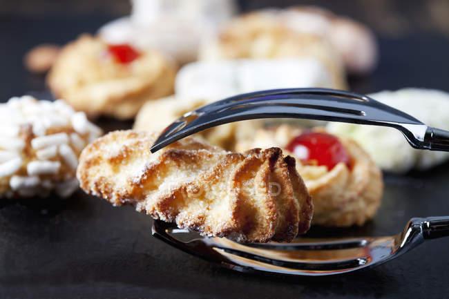 Primer plano de pinzas pastelería holding italiano galleta almendra - foto de stock