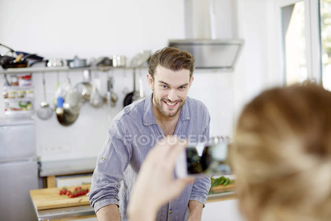 Woman taking cell phone picture of smiling man in kitchen — Stock Photo