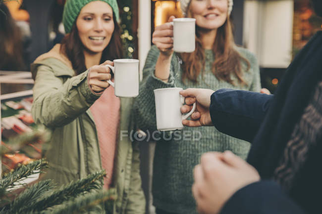 Happy friends clinking cups of hot punch on the Christmas Market — Stock Photo