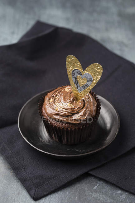 Cupcake with chocolate cream and golden powder, decorated — Stock Photo