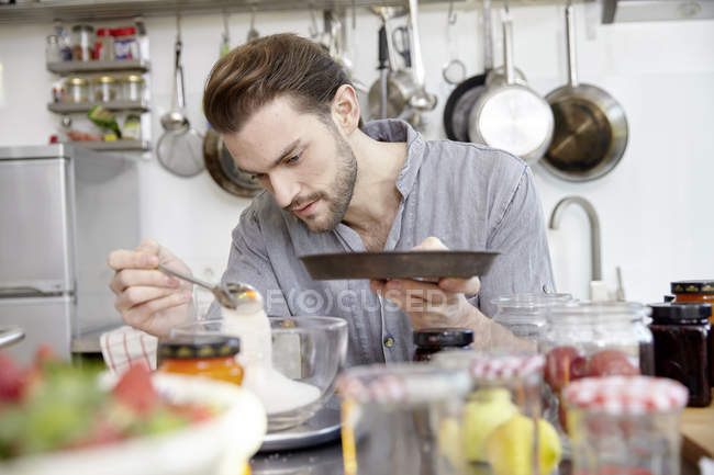 Young man preparing dough in kitchen — Stock Photo