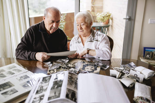 Senior couple watching their  old photos and photo albums at home — Stock Photo