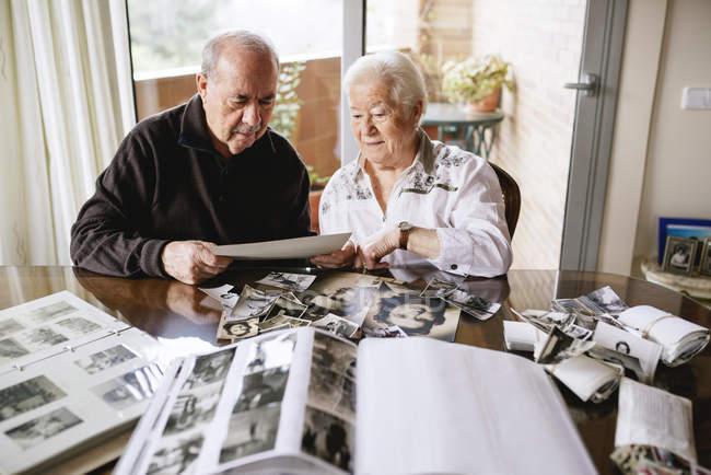 Старший пара, дивляться старі фотографії та фотоальбоми на дому — стокове фото