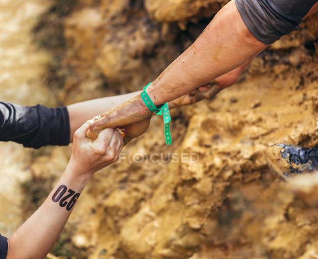Обрезанный образ участников экстремальной гонки препятствий, помогающих друг другу — стоковое фото