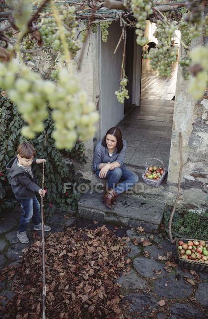 Woman sitting at entrance of country house with son picking autumn leaves — Stock Photo