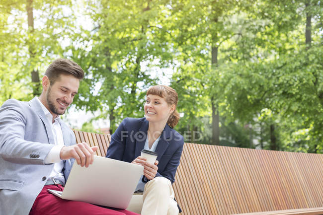 Tremendous Two Young Business People Sitting On Wooden Bench With Bralicious Painted Fabric Chair Ideas Braliciousco