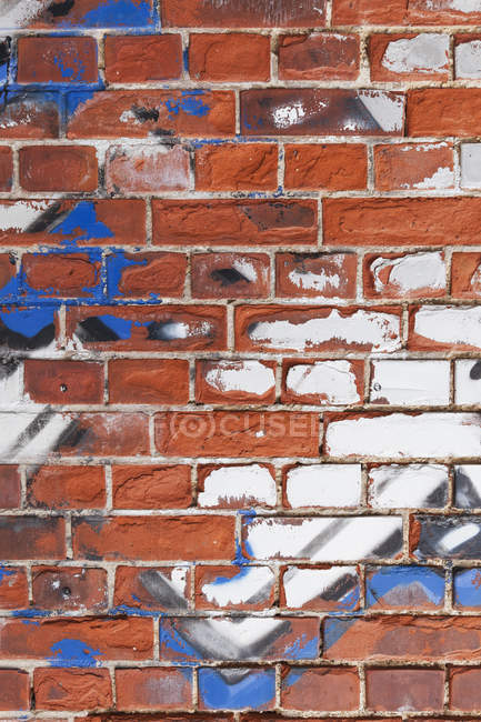 Old brick wall with remains of graffiti — Stock Photo