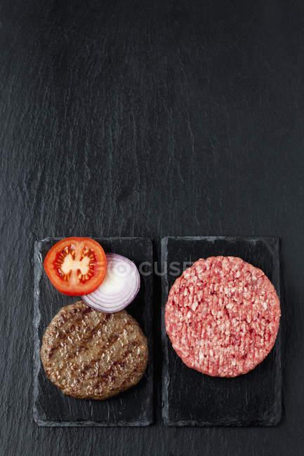 Hambúrgueres de carne frita e crua — Fotografia de Stock
