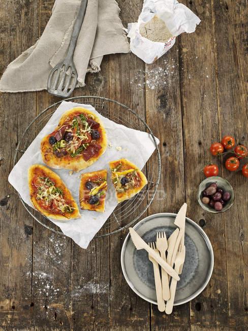 Pizza focaccia de la mezcla en refrigeración rack en madera oscura - foto de stock