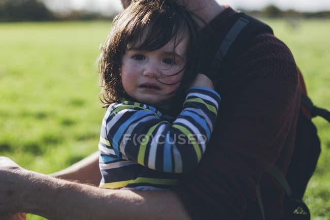Boy crying in his father's arms — Stock Photo