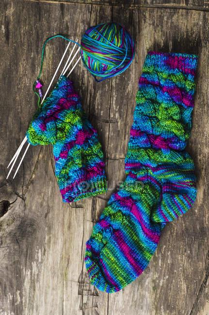 Красочные носки с шерстью и вязальными спицами на дереве — стоковое фото