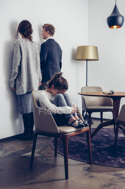 Sad girl sitting on a chair with her parents standing at a wall — Stock Photo