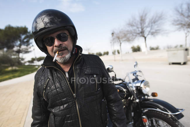 Portrait of smoking biker wearing helmet and sunglasses standing on a road in front of his motorcycle — Stock Photo