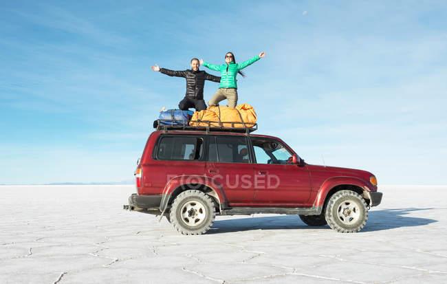 Coppia di Bolivia, Salar de Uyuni, inginocchiato su auto — Foto stock