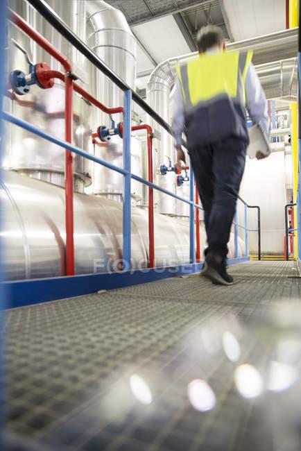 Людина носіння світловідбиваючого жилет ходити в індустріальному — стокове фото