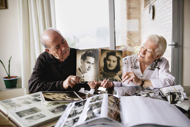 Senior couple showing old pictures of themselves — Stock Photo