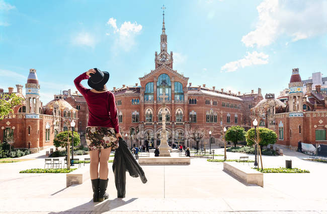 Spain, Barcelona, back view of woman looking at Sant Pau Art Nouveau Site — Stock Photo