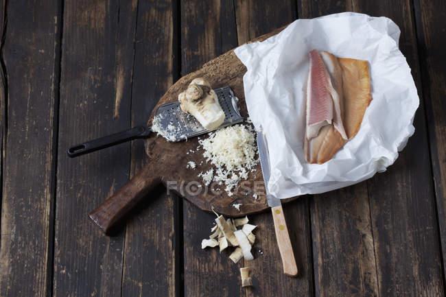 Rábano descascado e ralado e papel vegetal com filetes de truta defumada na placa de madeira — Fotografia de Stock