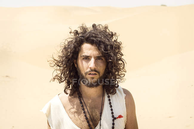 Man with beard and curly hair in desert — Stock Photo