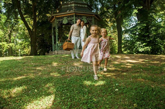 Glückliche Familie im Park, Eltern tragen Picknickkorb — Stockfoto