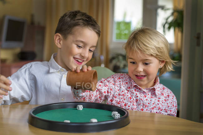 Brother and sister doing a game of dice together — two