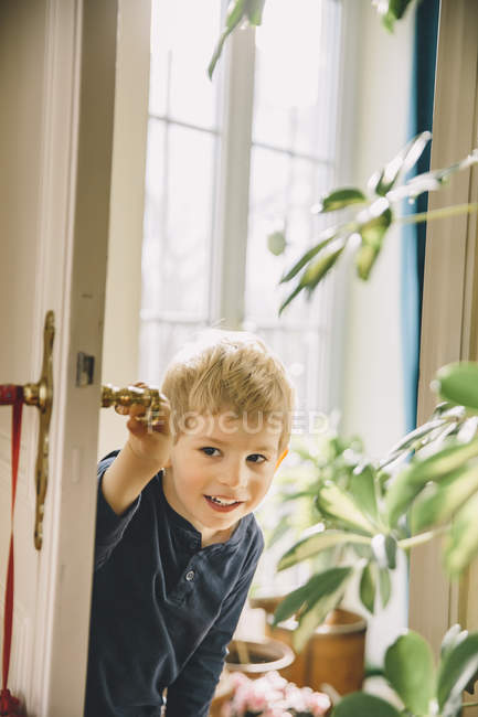 Curious Boy opening door in room at home — Stock Photo