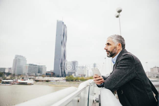 Empresario con pie de smartphone en Reichsbruecke mirando a distancia - foto de stock