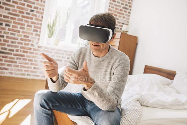 Чоловік сидить на ліжку в окулярах Віртуальна реальність — стокове фото