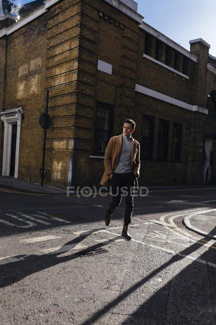 Young man crossing urban street — Stock Photo