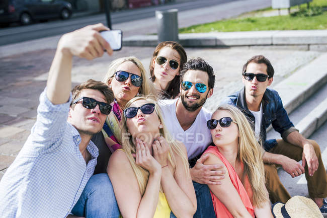 Happy friends wearing sunglasses taking a selfie outdoors — Stock Photo