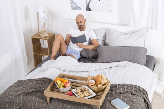 Hombre maduro con el libro y el desayuno en la cama - foto de stock