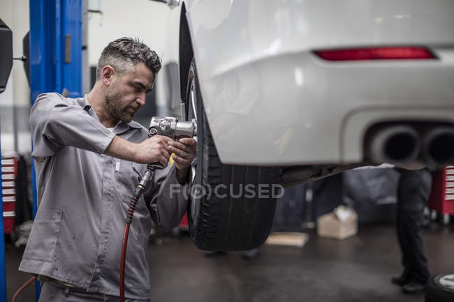 Car mechanic in a workshop changing tire — Stock Photo