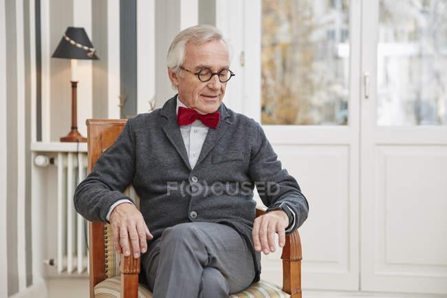 Homme âgé assis sur la chaise regardant smartwatch — Photo de stock